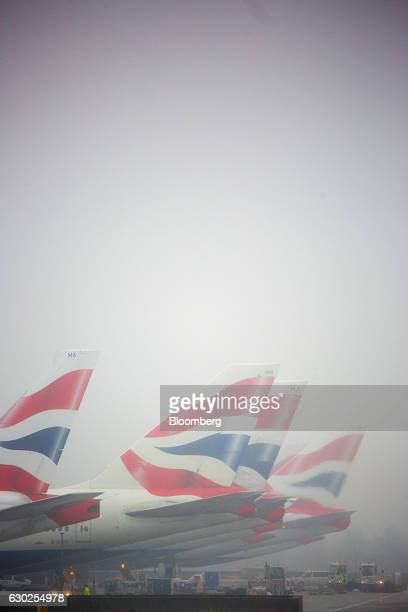 Tail fins on passenger aircraft operated by British Airways a unit of International Consolidated Airlines Group SA stand in fog at Terminal 5 at...