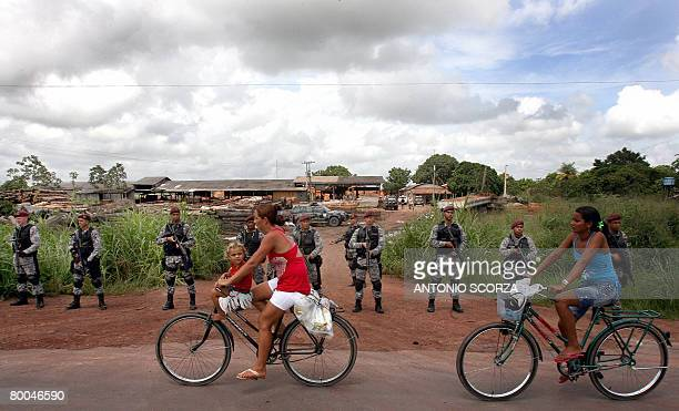 Tailandia residents pass by a line of National Force agents securing a suspicious sawmill in the outskirts of Tailandia Para northen Brazil on...