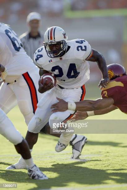 Tailback Carnell Williams of the Auburn Tigers runs with the ball as he tries to break throught the arms of strong safety Troy Polamalu of the USC...