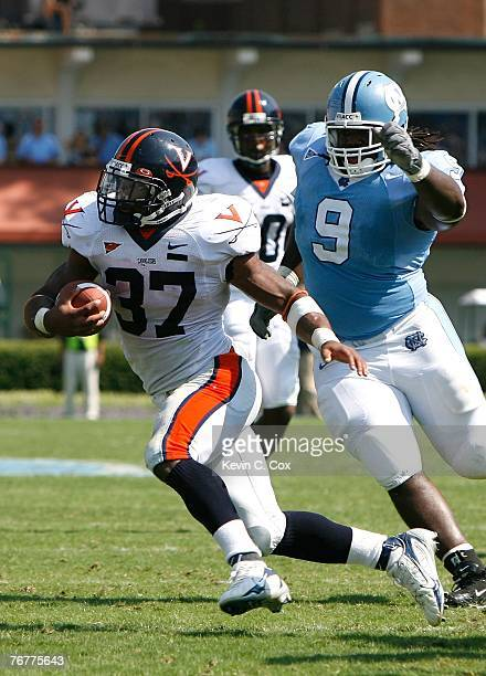 Tailback Cedric Peerman of the Virginia Cavaliers rushes away from defensive tackle Marvin Austin of the North Carolina Tar Heels during the...
