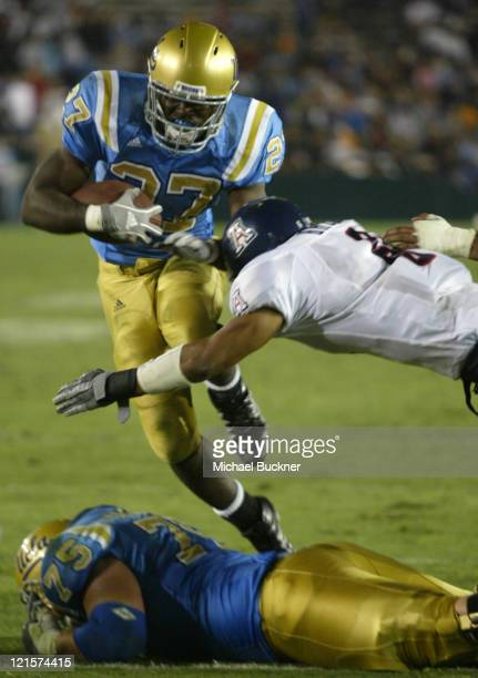 Tailback Chris Markey of UCLA jumps over lineman Robert Cleary before being stopped by defensive back Darell Brooks for extra yardage during the of...