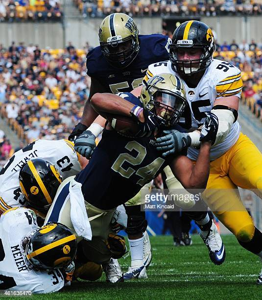 Tailback James Conner of the University of Pittsburgh Panthers dives forward with the football against defensive linemen Nate Meier and Drew Ott and...