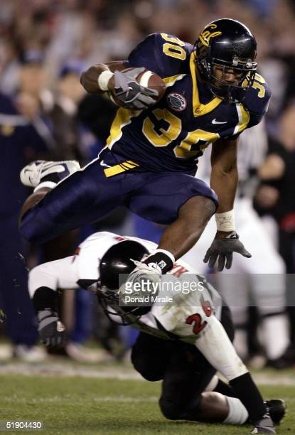 Tailback JJ Arrington of the California Golden Bears hurdles over the tackle of cornerback Khalid Naziruddin of the Texas Tech Red Raiders during the...