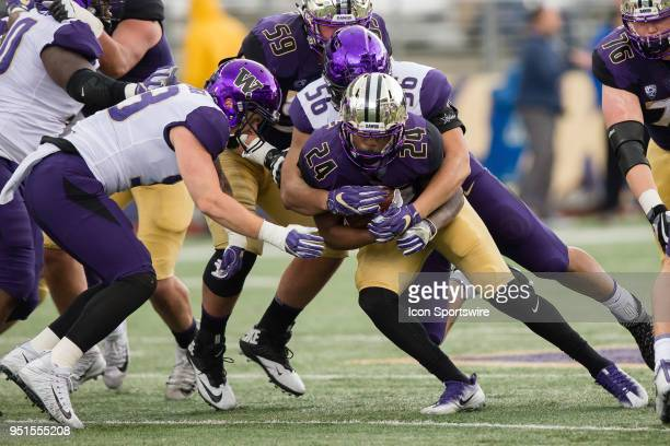 Tailback Kamari Pleasant is tackled by linebacker Nick Harris during the University of Washington Spring Game at Husky Stadium on Saturday April 21...