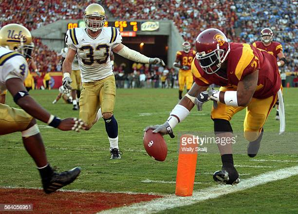 USC tailback LenDale White score a touchdown in the third as UCLA defenders Jarrad Page and Christian Taylor look on at the Coliseum Saturday