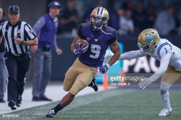 Tailback Myles Gaskin of the Washington Huskies rushes against defensive back Darnay Holmes of the UCLA Bruins at Husky Stadium on October 28 2017 in...