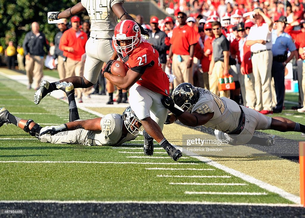 Tailback Nick Chubb #27 of the Georgia Bulldogs is pulled out of bounds by Nigel Bowden #52 of the Vanderbilt Commodores just short of the end zone during the second half at Vanderbilt Stadium on September 12, 2015 in Nashville, Tennessee.