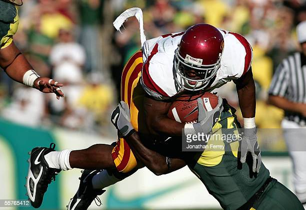 Tailback Reggie Bush of the USC Trojans is tackled by cornerback Justin Phinisee of the Oregon Ducks on September 24 2005 at Autzen Stadium in Eugene...