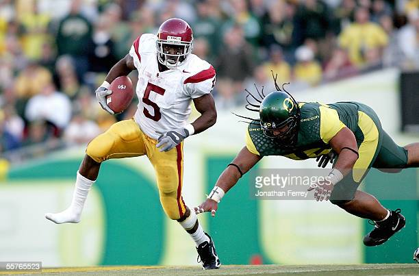Tailback Reggie Bush of the USC Trojans loses his shoe as he outruns defensive tackle Matt Toeaina of the Oregon Ducks on September 24 2005 at Autzen...
