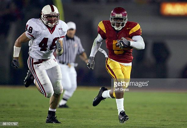 Tailback Reggie Bush of the USC Trojans outruns linebacker Mike Silva of the Stanford Cardinal for a touchdown during the first quarter of the game...