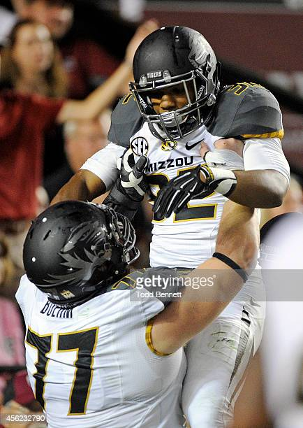 Tailback Russell Hansbrough is congratulated by offensive lineman Evan Boehm after scoring a touchdown against the South Carolina Gamecocks during...