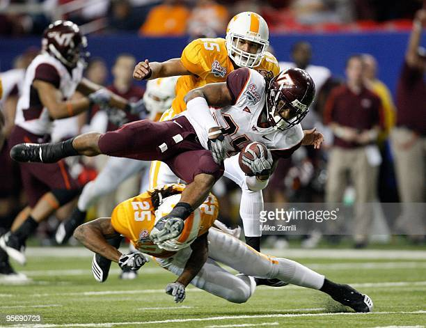 Tailback Ryan Williams of the Virginia Tech Hokies is tackled by defensive back Art Evans of the Tennessee Volunteers while Evans' teammate and...