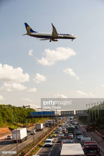 Tailbacks on the M1 motorway in the East Midlands caused by roadworks with a plane coming in to land at East Midlands airport, UK.