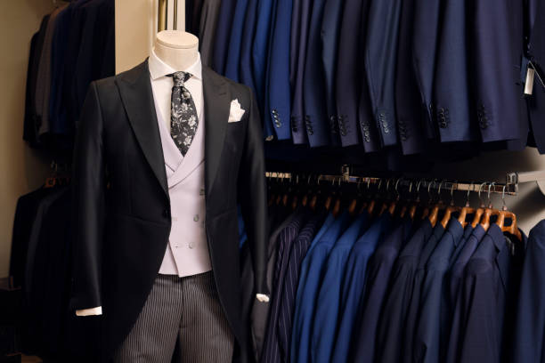 Tailcoat withformal striped trouserson mannequin and blazers on rack in tailors boutique