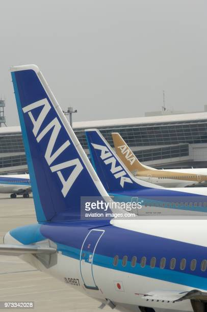 tailfins of an ANA All Nippon Airways Airbus A320200 Boeing 737 and an ANK 737 parked at the terminal and taxiing behind