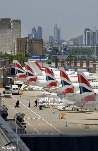 Tailfins of British Airways BA CityFlyer Embraer 170s parked in a row at London City with skyscrapers behind