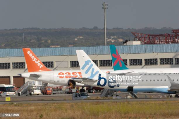tailfins of Flybe British European Embraer 195LR with baggagebelt truck and airstairs First Choice Airways Boeing 757 easyJet Airbus A319100 parked...