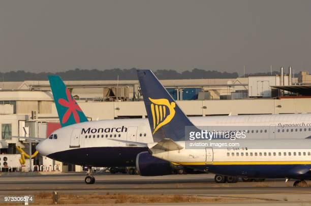 tailfins of Ryanair Boeing 737800 and First Choice Airawys 757200 parked with nose of Monarch Airlines Airbus A300600R taxiing at Palma International