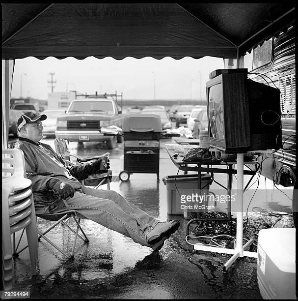 Tailgater Joe Hammond sits in the rain watching the Miami Dolphins play against the Philadelphia Eagles on his make shift tv in the stadium carpark...