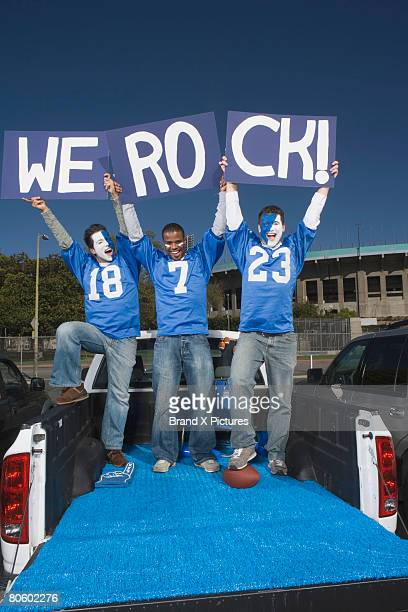 tailgating fans holding signs - football body paint stock photos and pictures