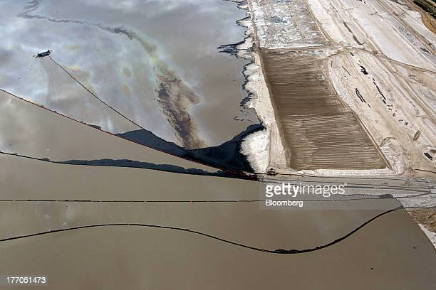 A tailings pond sits at a Suncor Energy Inc oil sands mining operation near Fort McMurray Alberta Canada on Tuesday Aug 13 2013 Canadian oil...