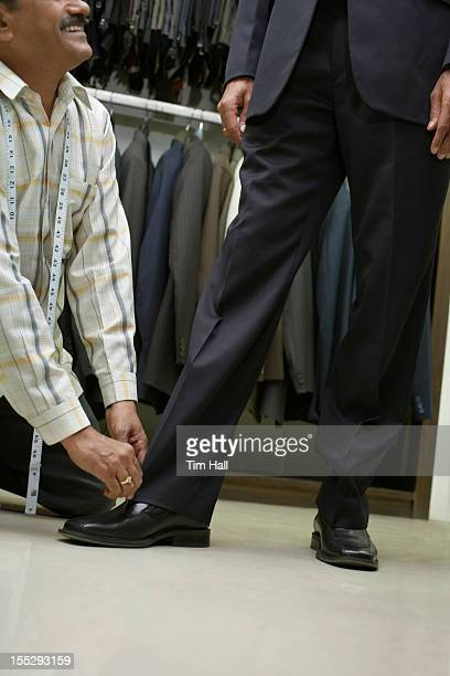 Tailor adjusting mans pants