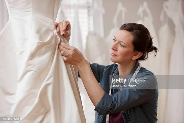 Tailor adjusting wedding dress