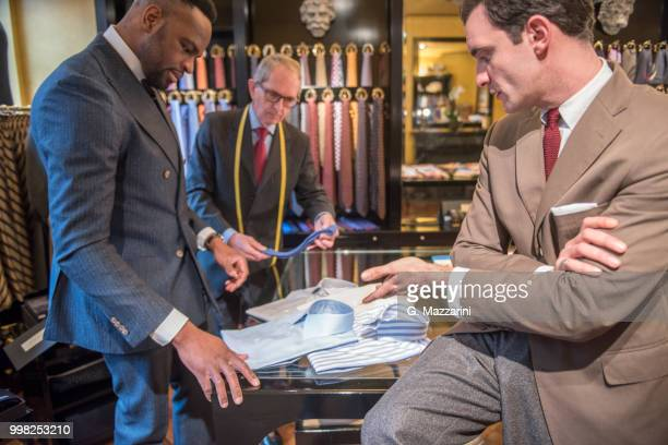 tailor and customer looking at shirts in tailors shop - custom tailored suit stock pictures, royalty-free photos & images