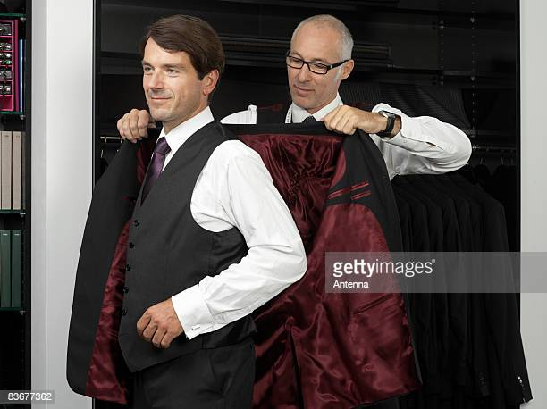 A tailor assisting a man trying on a suit