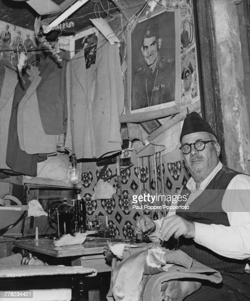 A tailor at work in his shop in a souq or marketplace in Baghdad Iraq circa 1960 Behind him is a portrait of Iraqi Prime Minister Abd alKarim Qasim