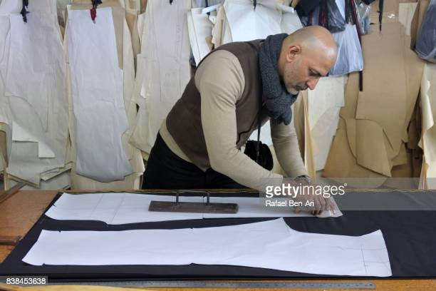 Tailor chalking measurements in tailors shop studio