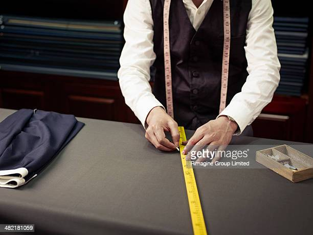 Tailor chalking measurements in traditional tailors shop