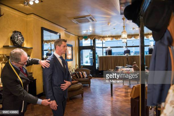 tailor checking sleeve on customer's suit jacket - custom tailored suit stock pictures, royalty-free photos & images