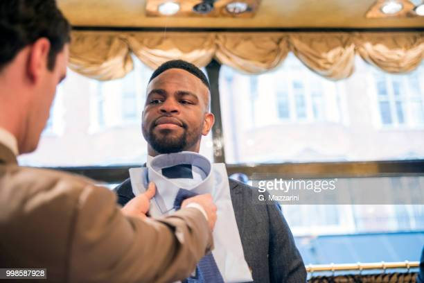 tailor coordinating shirt and tie for customer in tailors shop - custom tailored suit stock pictures, royalty-free photos & images
