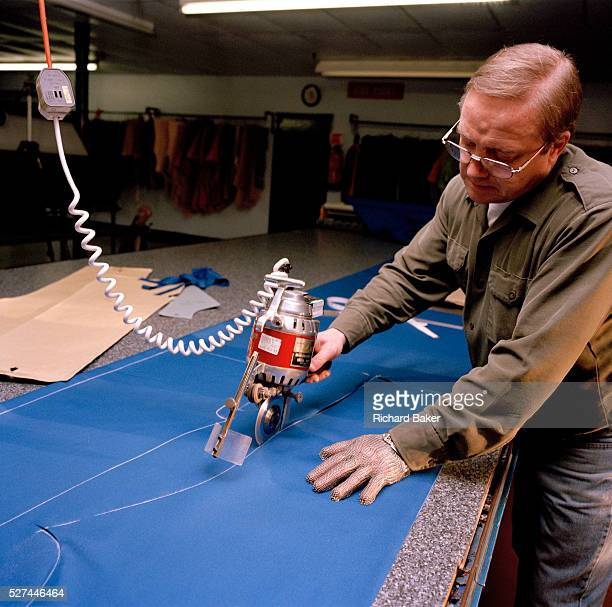 A tailor cuts red material for flying suits for the elite 'Red Arrows' Britain's prestigious Royal Air Force aerobatic team The man is a bespoke...