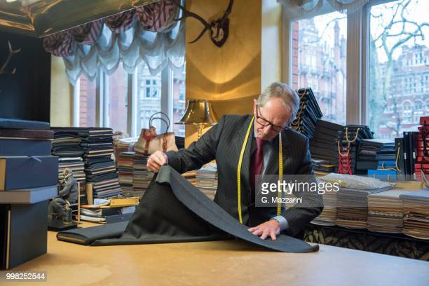 tailor examining roll of cloth in tailor shop - custom tailored suit stock pictures, royalty-free photos & images