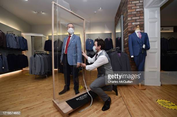 Tailor Gary Keenan of Bogart Menswear measures up a suit using a customer pod designed to keep customers safe from Covid-19 after their store...