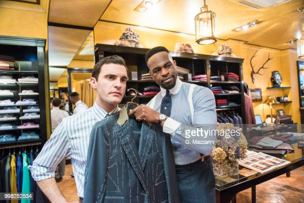 tailor holding bespoke suit jacket against customer in tailors shop - custom tailored suit stock pictures, royalty-free photos & images