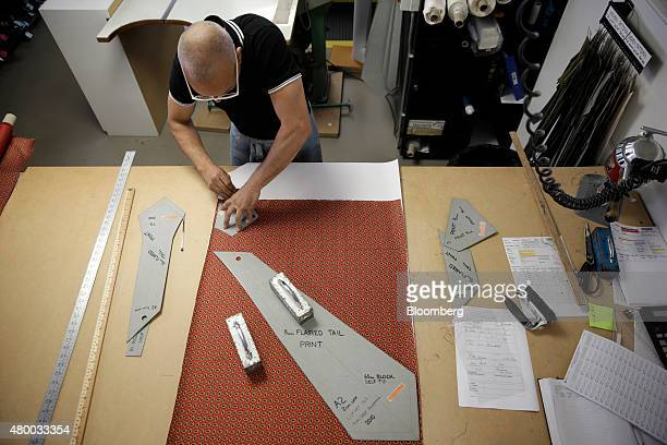 A tailor holds a template as he chalks a piece of silk fabric before stitching a tie at Drake's factory outlet store in London UK on Friday June 26...