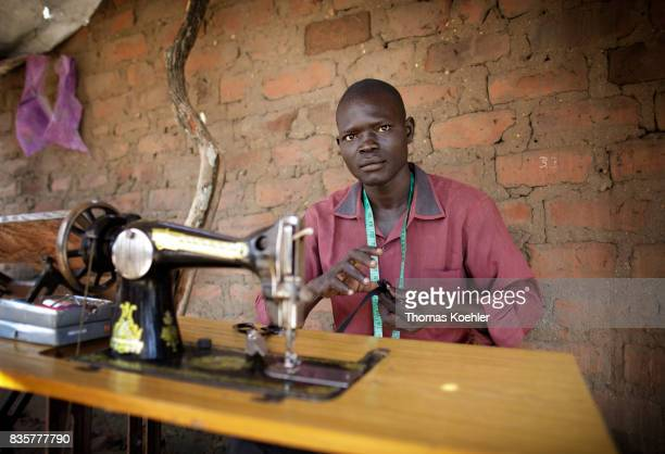 A tailor is working on his sewing machine at Rhino Refugee Camp Settlement in northern UgandaThe area is home to about 90000 refugees from South...