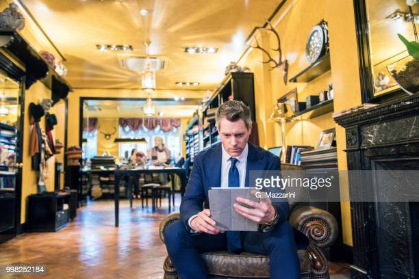 tailor looking at digital tablet in tailors shop - custom tailored suit stock pictures, royalty-free photos & images