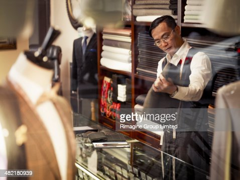 Tailor looking at fabric in traditional tailors shop