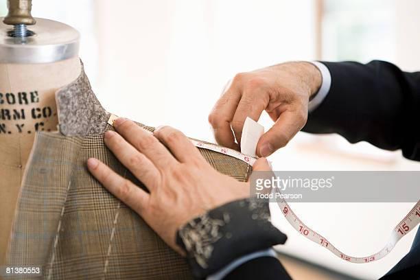 Tailor measures and chalks jacket shoulder