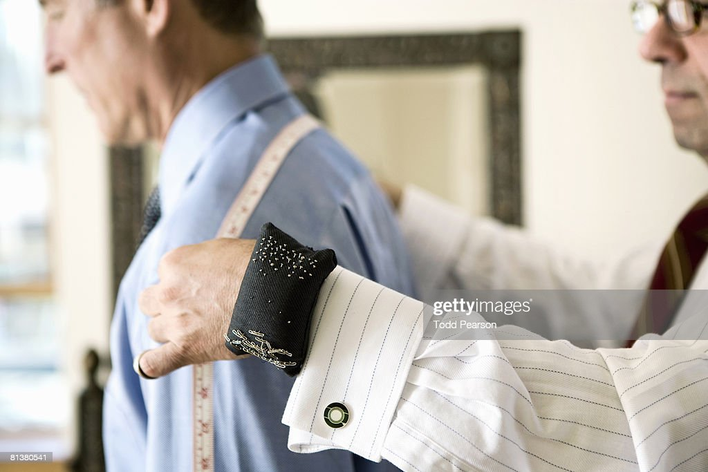 Tailor measures man's shoulders : Stock Photo