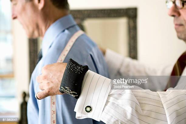 Tailor measures man's shoulders