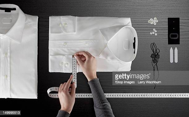 a tailor measuring a button down shirt, focus on hands - top garment stock photos and pictures