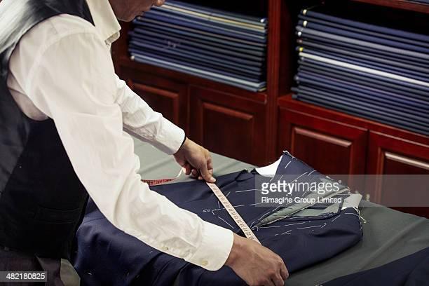 tailor measuring garment in tailors shop - top garment stock-fotos und bilder