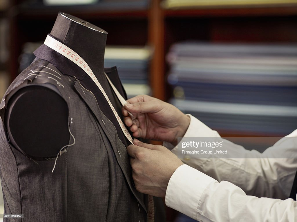 Tailor measuring garment in traditional tailors shop : Stock Photo