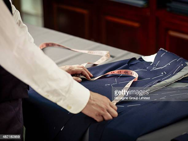 Tailor measuring garment on table in traditional tailors shop