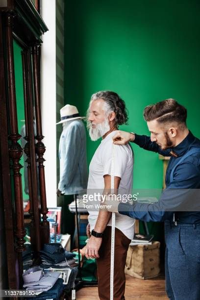 tailor measuring up customer for suit - custom tailored suit stock pictures, royalty-free photos & images